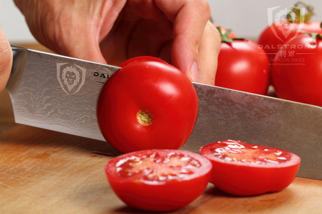 Close up of kitchen knife slicing through tomatoes on a wooden surface