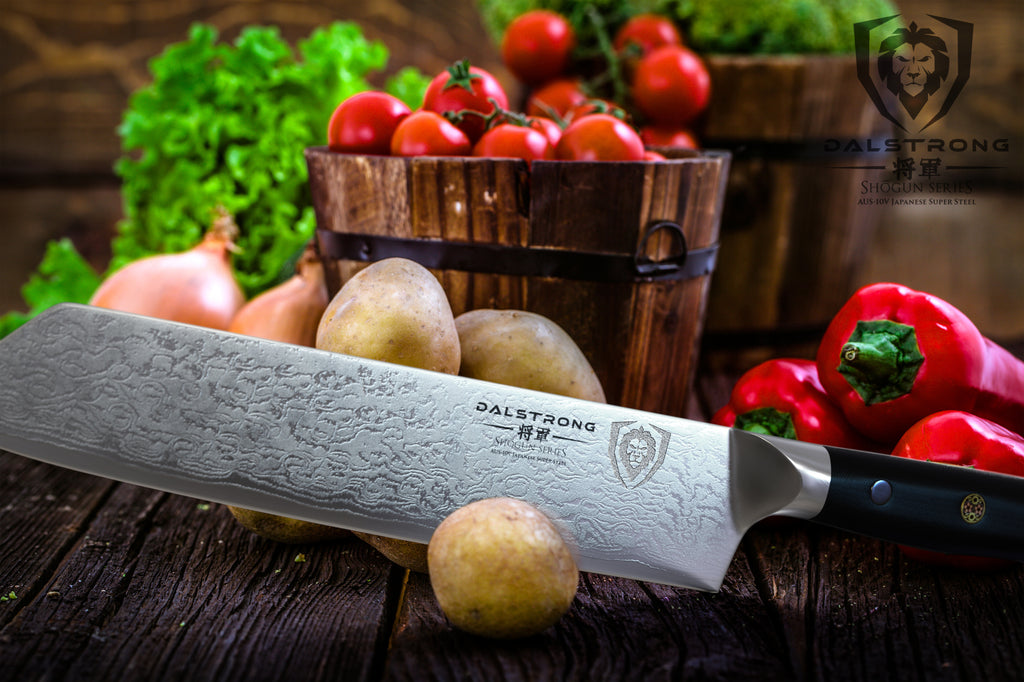 Kiritsuke knife with damascus steel chopping a small potato with more produce in the background