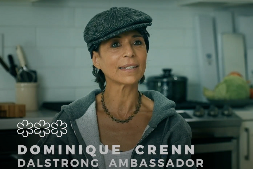 Chef Dominique Crenn sitting down in a kitchen giving an interview with subtitles of her name