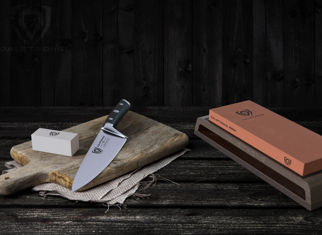 Dalstrong Premium Whetstone Kit on a wooden table next to a cutting board with a chef knife on it