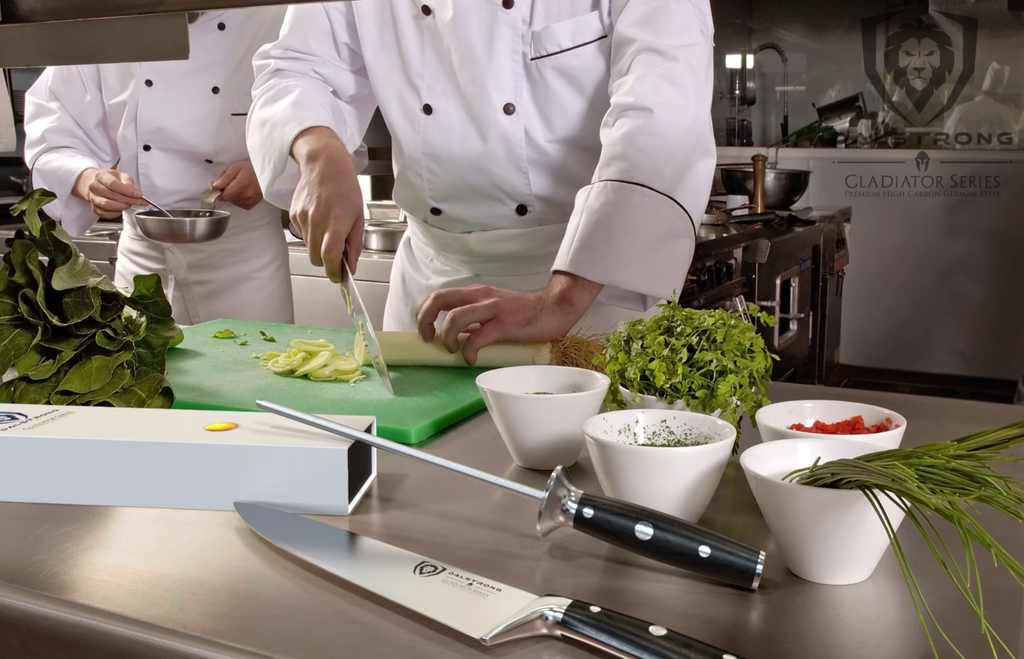 A busy chef kitchen with a knife and honing steel in the foreground