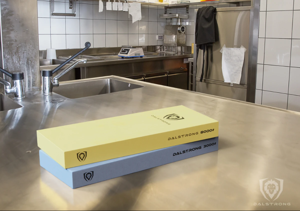 A yellow and blue knife sharpening whetstone on an industrial kitchen surface with an apron hanging in the background