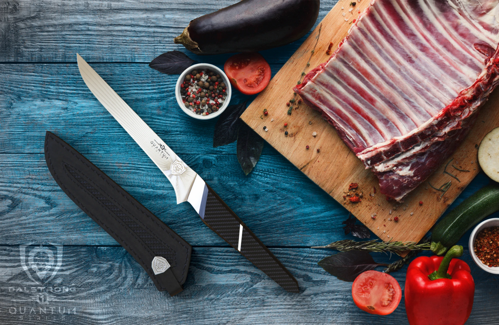 Sharp boning knife with black handle next to a wooden cutting board that has a rack of ribs on top of it