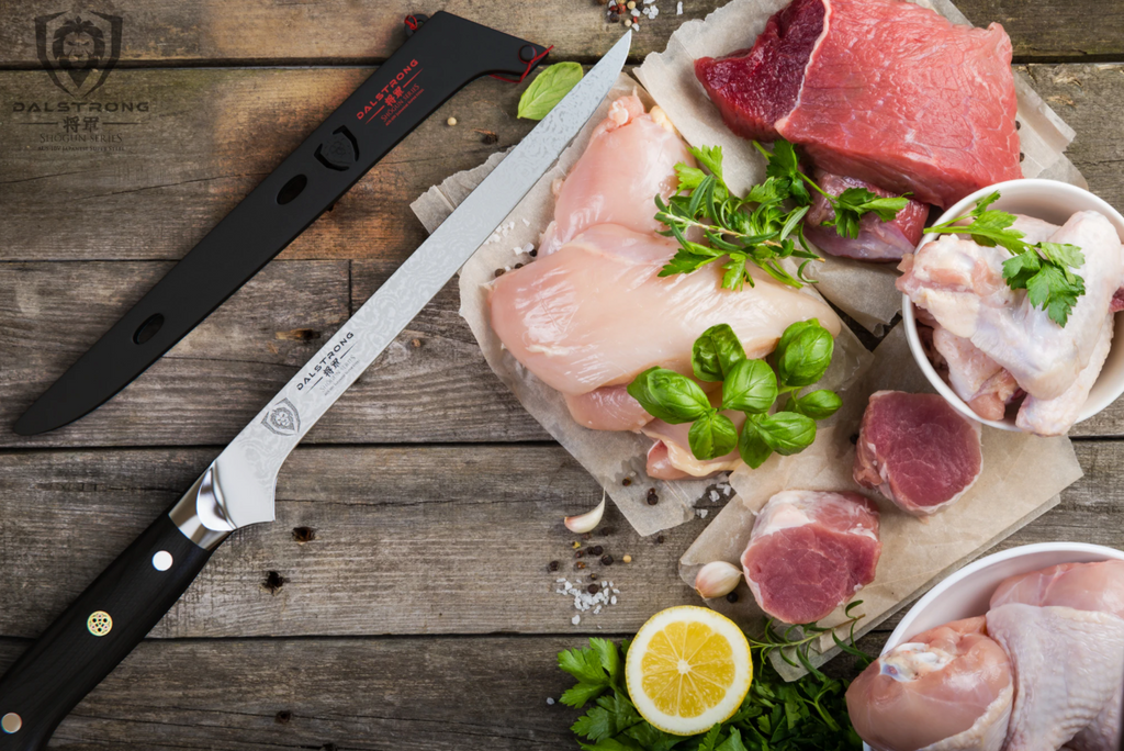 Boning knife on a wooden surface next to uncooked chicken and meat that are on parchment paper beside vegetables