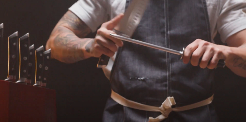 A Chef in a blue apron honing his knife against a sharpening steel with a knife block set next to him