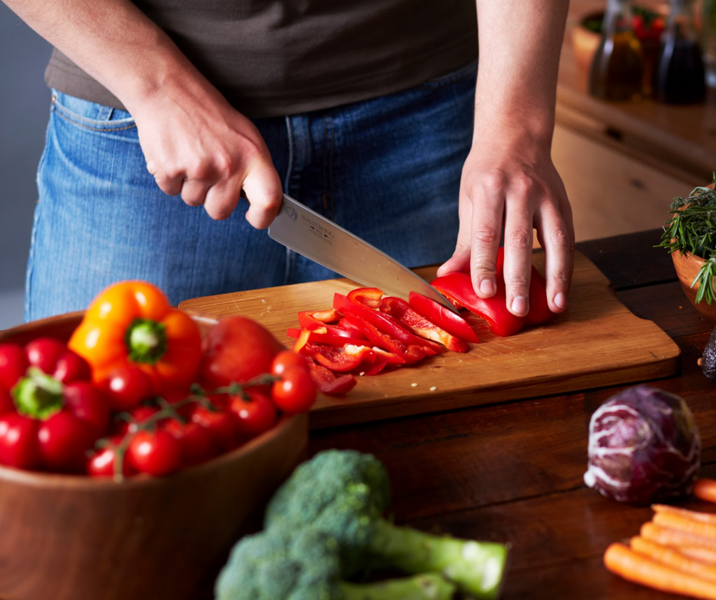 A man chops red peppers with a sharp kitchen knife on a wooden cutting board