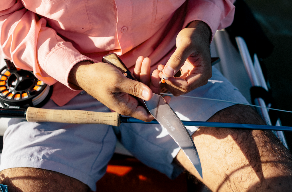 Close up of man in shorts holding a sharp fillet knife