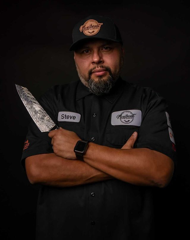 Chef Steve Hernandez in a black tshirt with his arms folded holding a Dalstrong knife