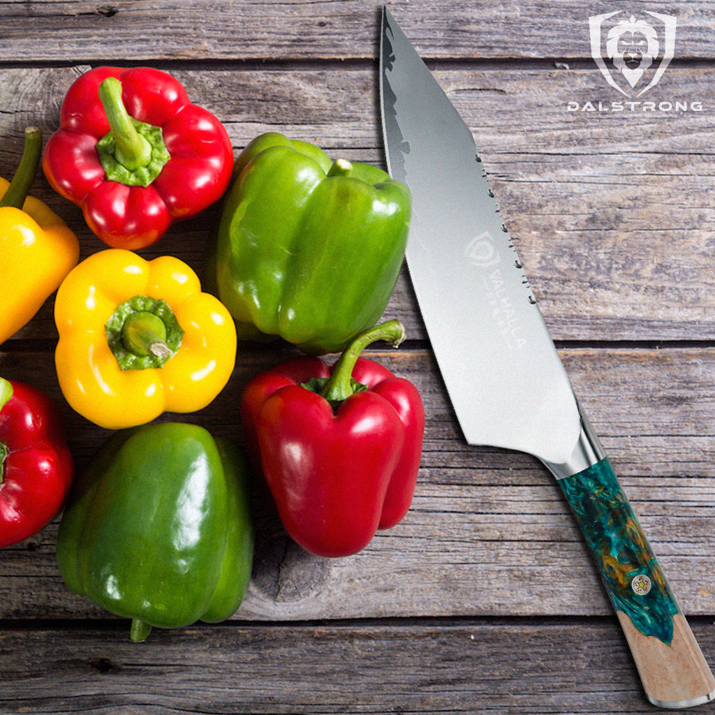 A pile of colourful red green and yellow peppers on a wooden surface next to a sharp kitchen knife