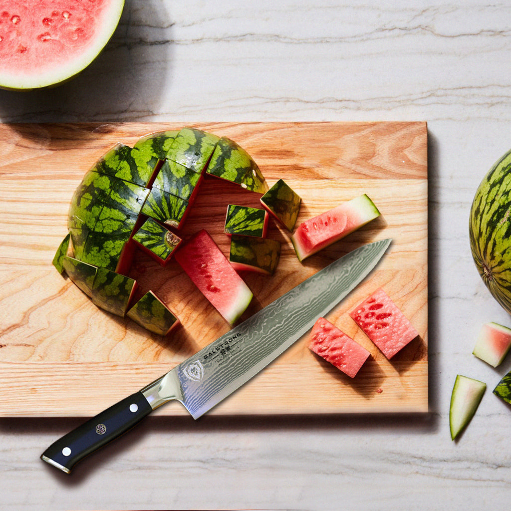 A partly chopped watermelon on a wooden cutting board next to a sharp kitchen knife