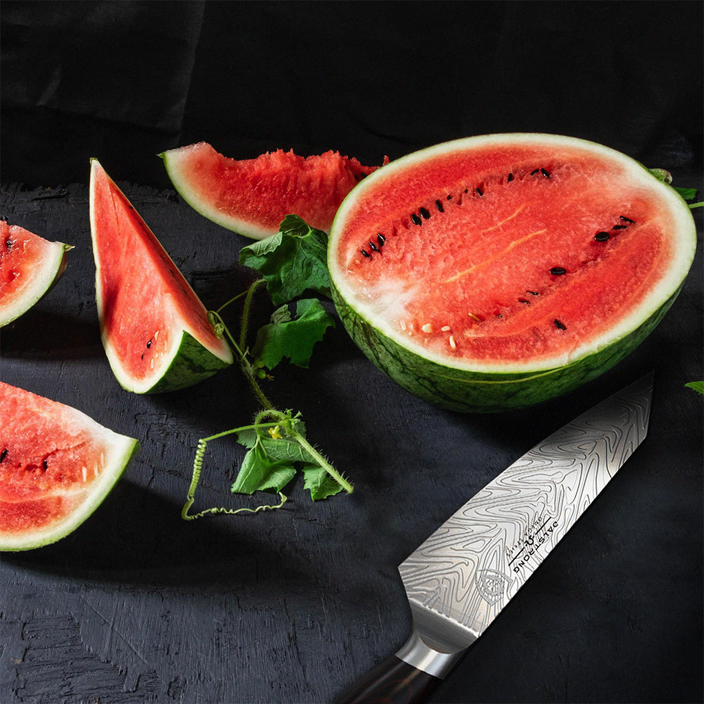 Several pieces of watermelon against a dark surface next to a chef's knife