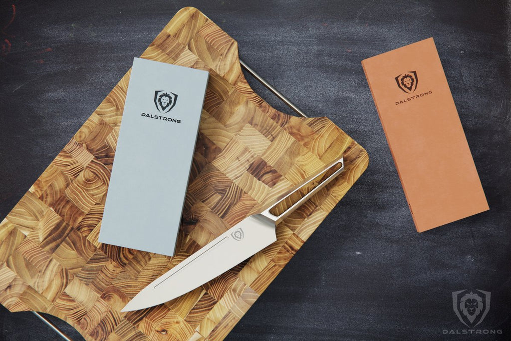 Stainless Steel Knife and a grey whetstone rest on a large wooden cutting board with a second whetstone on the table next to the board