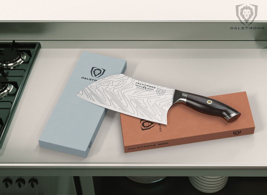 A Dalstrong cleaver resting across two whetstones on a kitchen surface