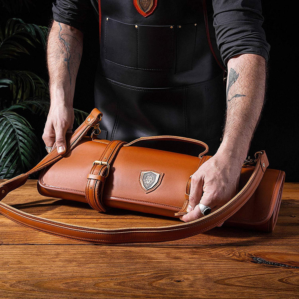 Man in black apron zips up a brown leather knife roll on a wooden table