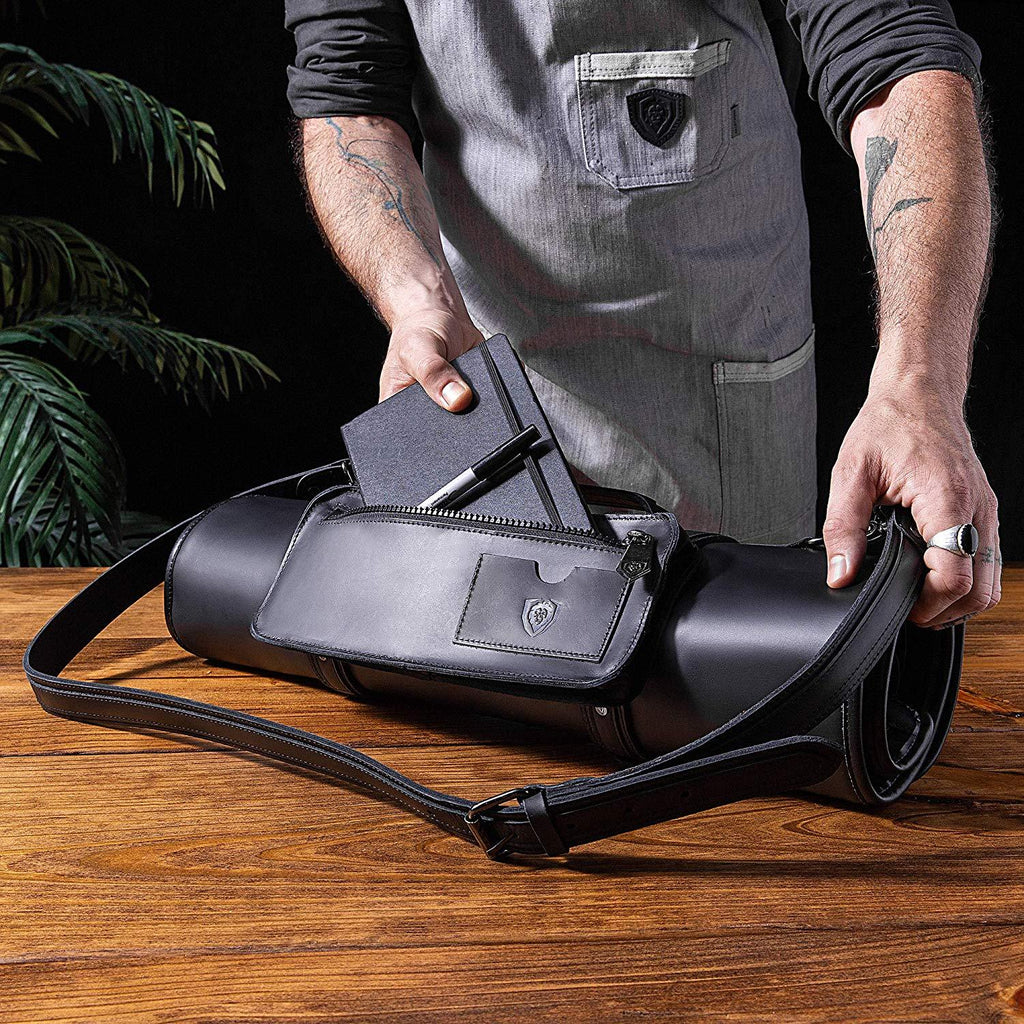 A chef places a leather book into his black leather knife roll on a wooden table