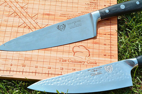 Chef's knives on wooden cutting board outside on the grass