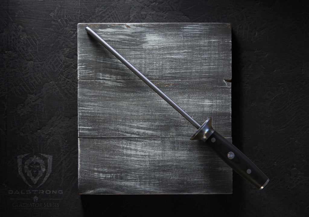 Dalstrong Gladiator Series Honing Rod Resting on a dark grey cutting board with a black background.