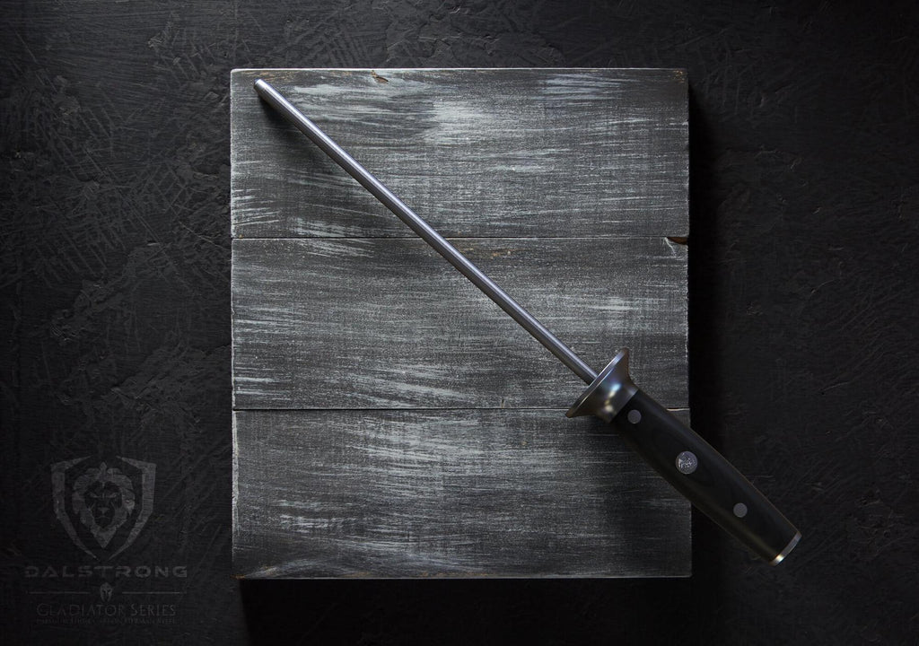 A sharpening steel with a black handle rests on a dark grey cutting board against a black background