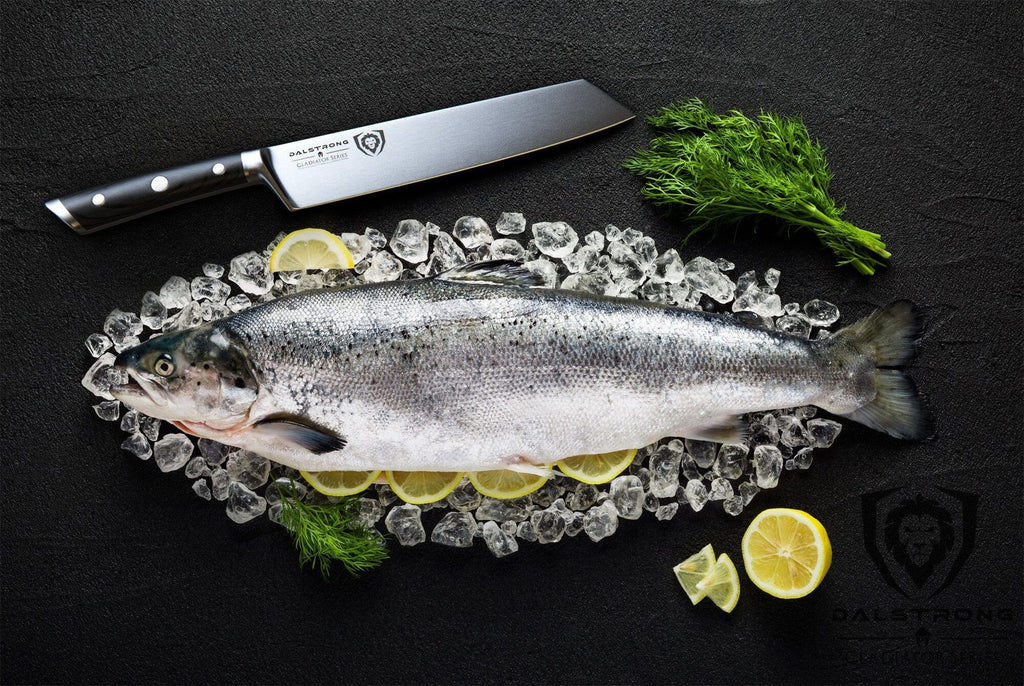 Large uncooked fish against a black surface next to a sharp kiritsuke knife