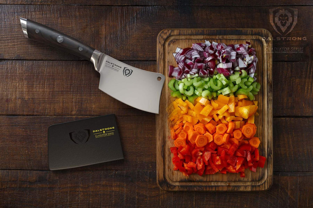 Mini cleaver with black handle next to a cutting board filled with chopped vegetables of different colors