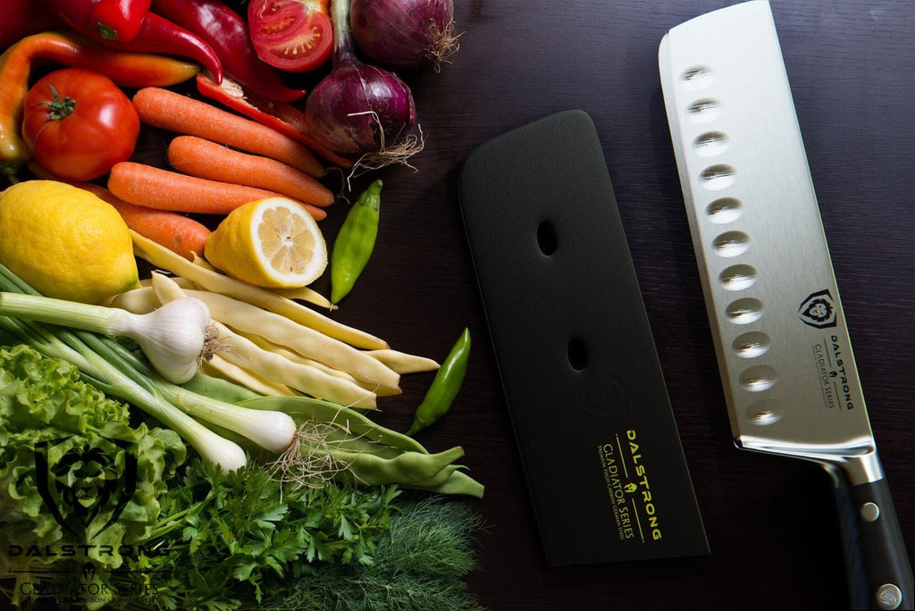 A variety of vegetables against a dark surface next to a sharp nakiri knife