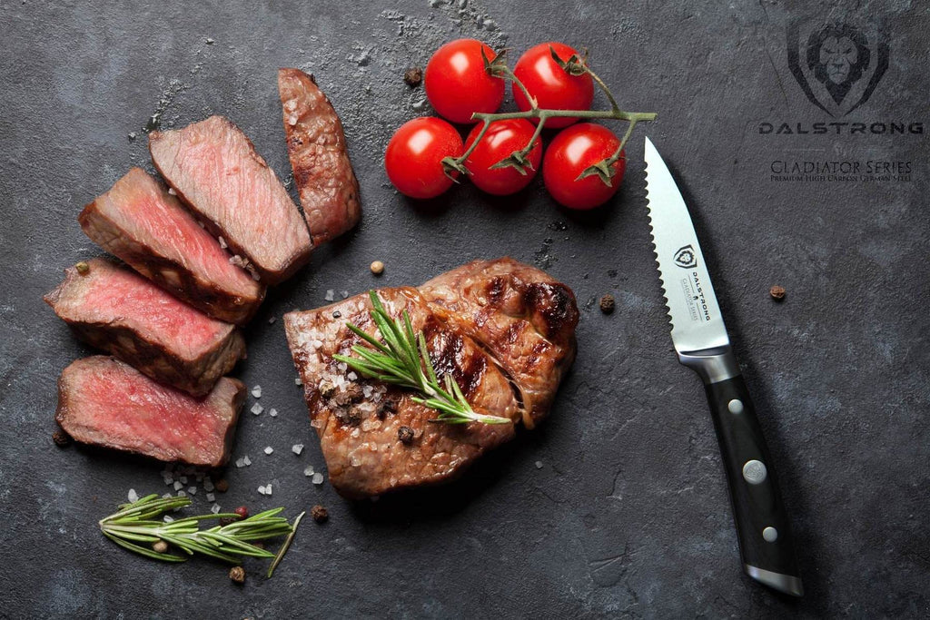 A serrated paring knife next to several slices of medium rare steak and cherry tomatoes