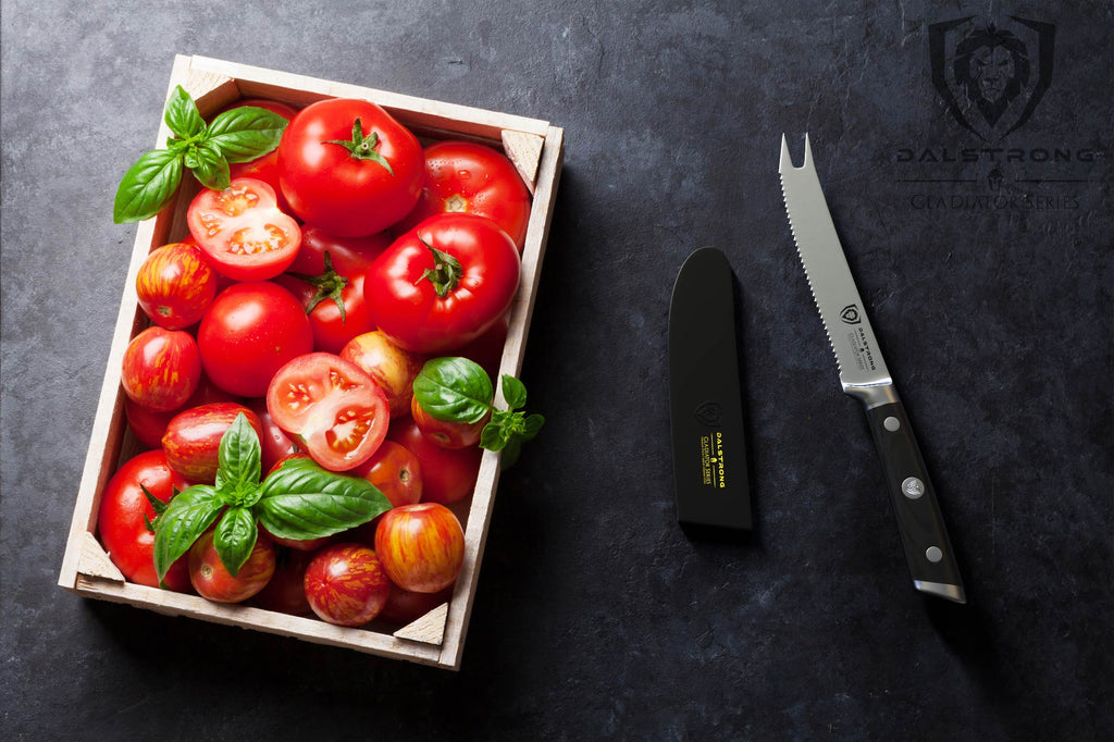 A grocery crate of tomatoes against a dark background next to a serrated tomato knife
