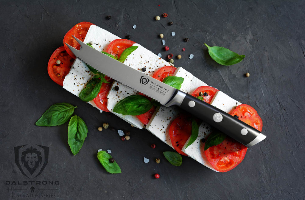 A serrated knife balancing on a bed of cheese and sliced tomatoes against a black backdrop