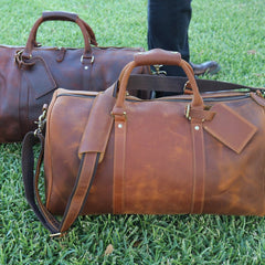 Two brown leather bags placed on grass