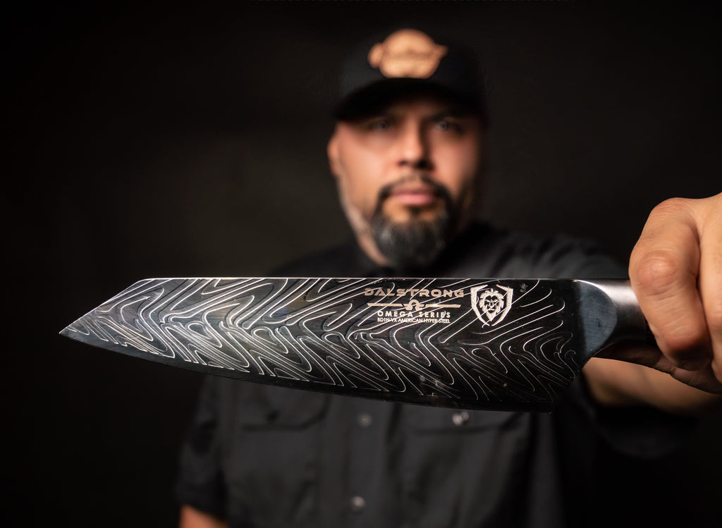 Chef Steve Hernandez in black clothes and blackgrond holding a Dalstrong blade to the camera