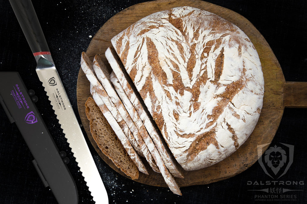 Circular loaf of bread on a cutting board next to a bread knife on a dark surface