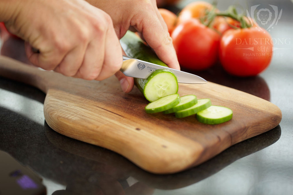 Hands using a paring knife to slice a cucumber on a wooden cutting board