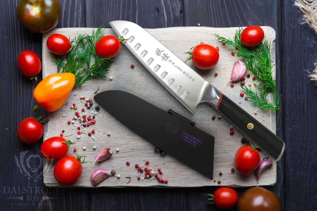 Japanese Style Santoku Knife on a cutting board next to cherry tomatoes garlic and other garnish
