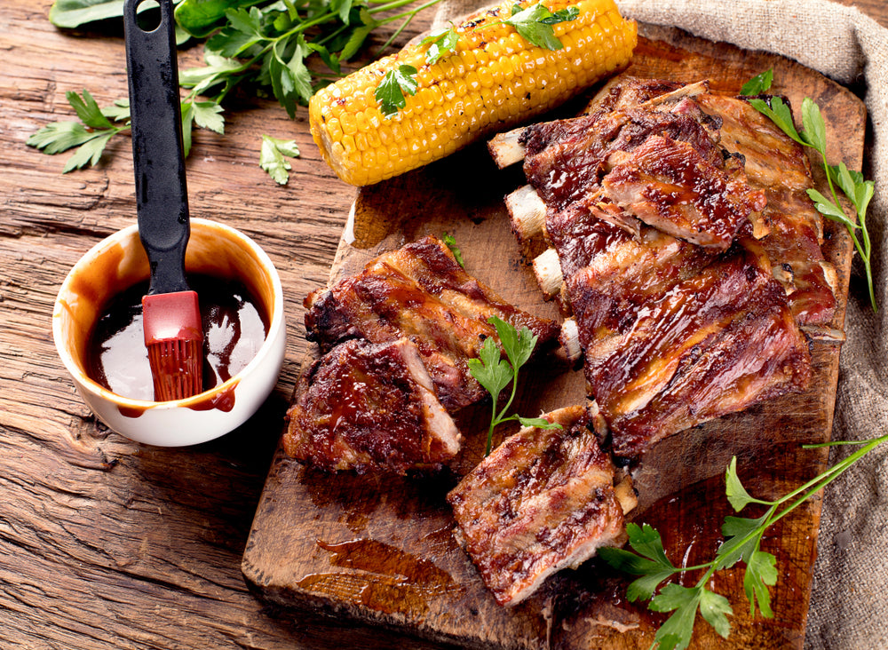 A rack of ribs on a cutting board next to a piece of corn on the cob