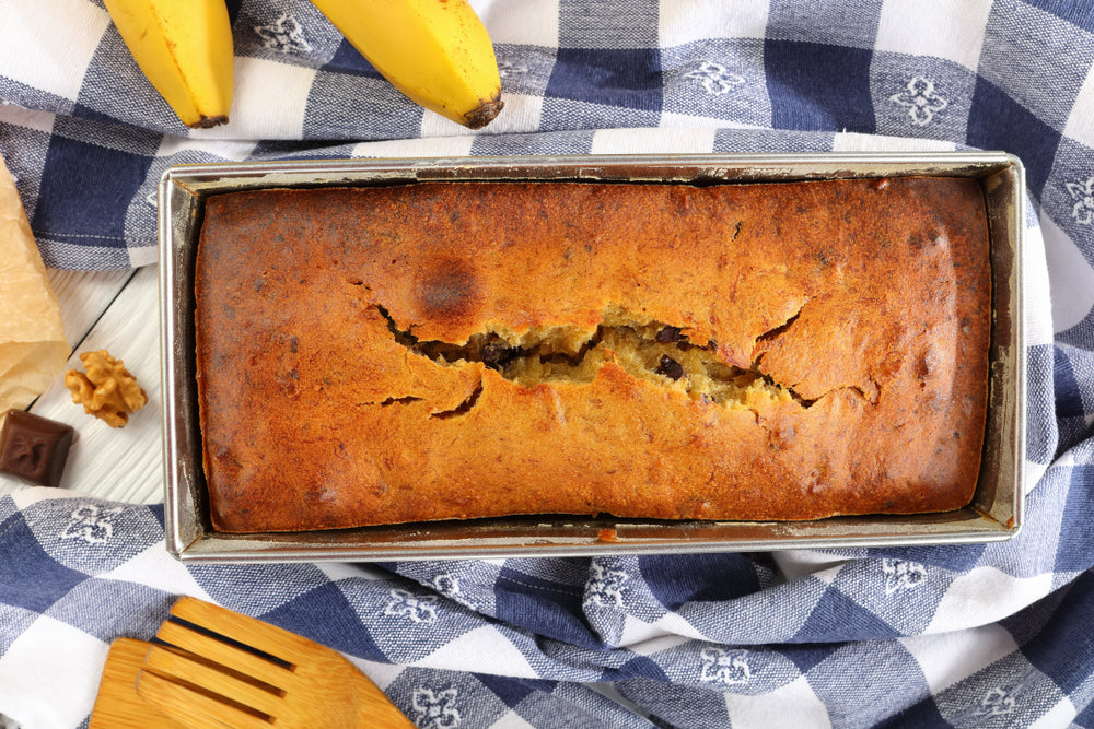 close-up of baked banana bread with walnuts and chocolate pieces in a loaf pan with kitchen towel, ripe bananas and ingredients on wooden table, authentic recipe, view from above