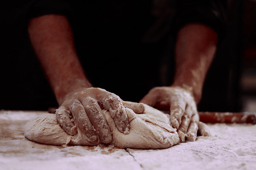 Man with sleeves rolled up kneading dough on a hard surface