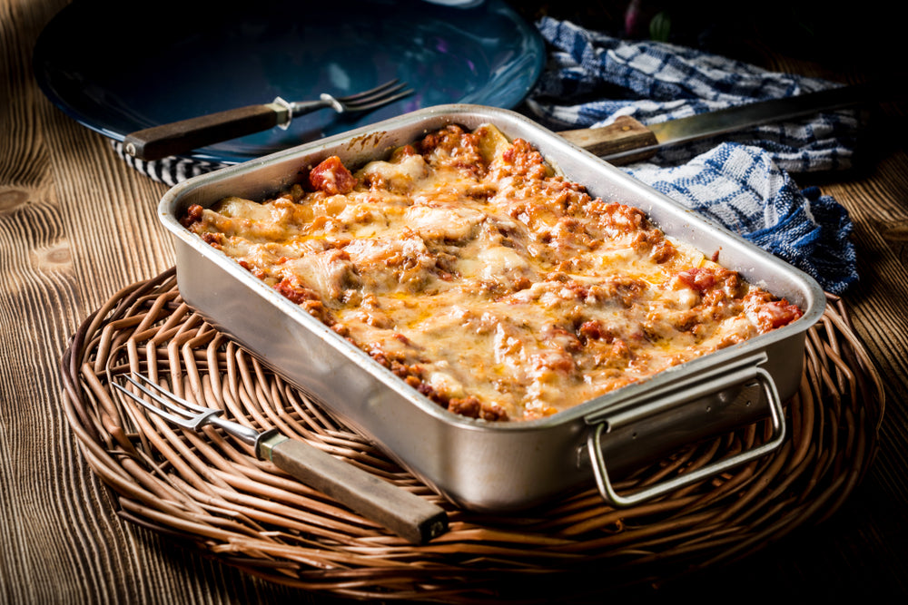 Baking tray filled with cooked lasagne on a brown table