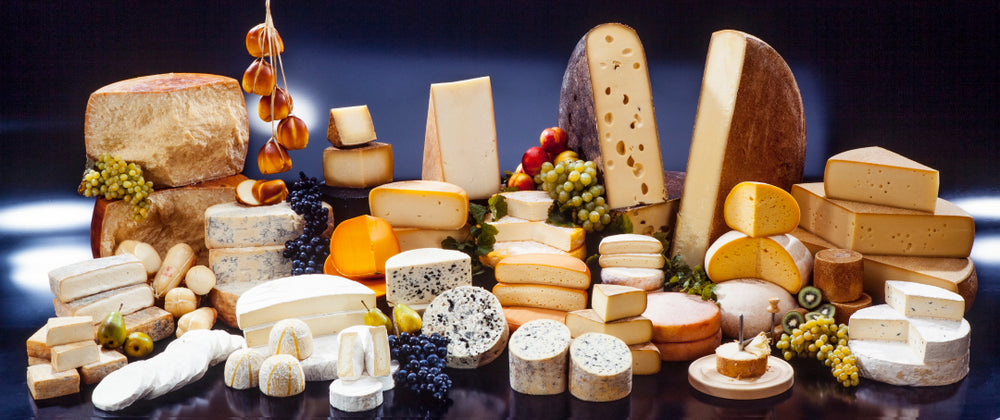 An enormous selection of international cheeses against a dark blue background