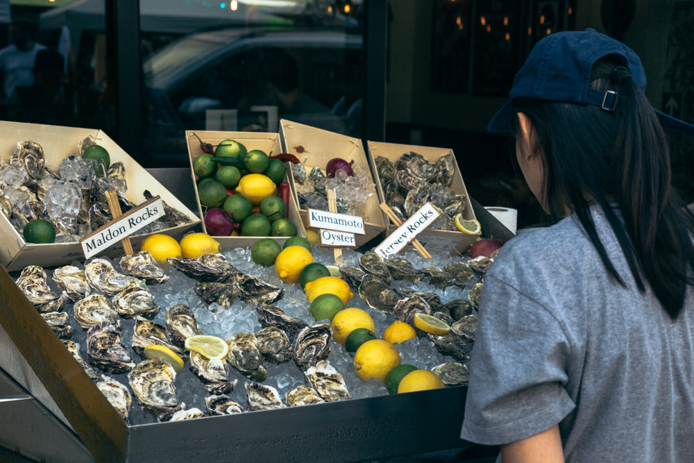 Woman in a hat choosing oysters at an outdoor market
