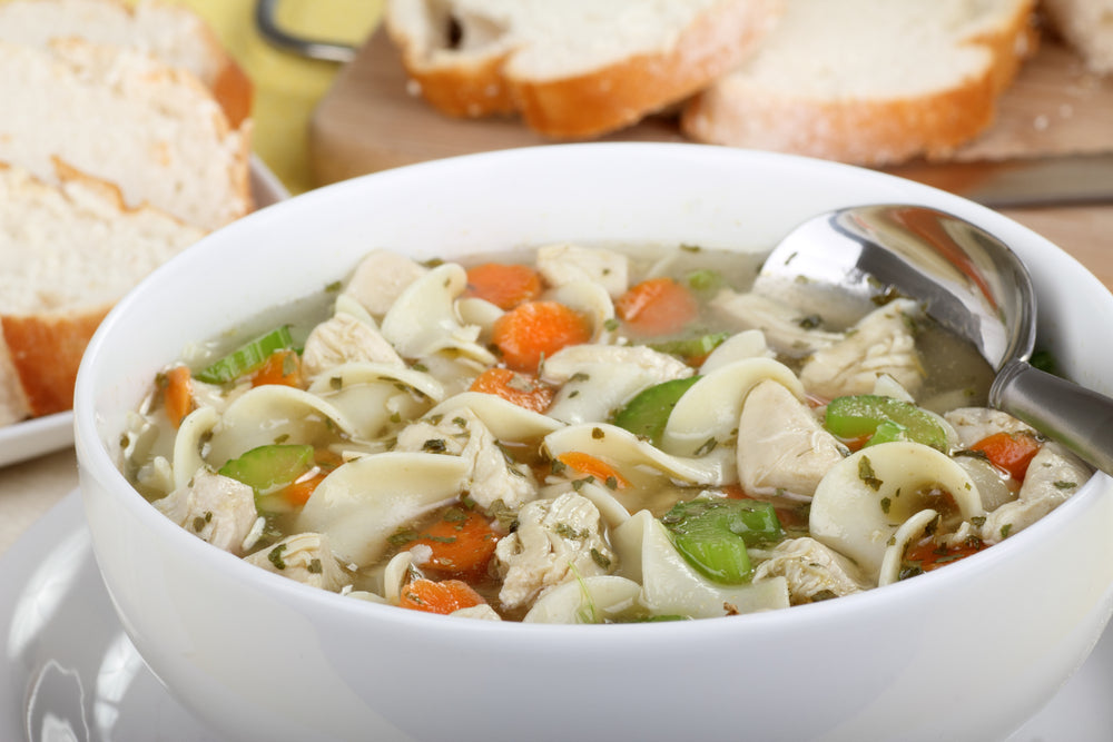 Close up of white bowl with chicken noodle soup and silver spoon on a kitchen table