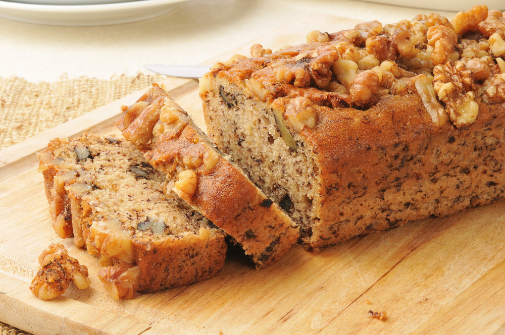 Banana bread seasoned with nuts on a brown cutting board