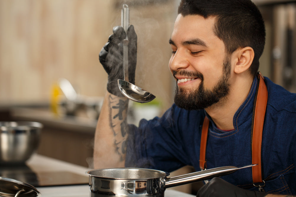 A tattooed chef smiles as he tastes a recipe from a ladle he has lifted from a saucepan