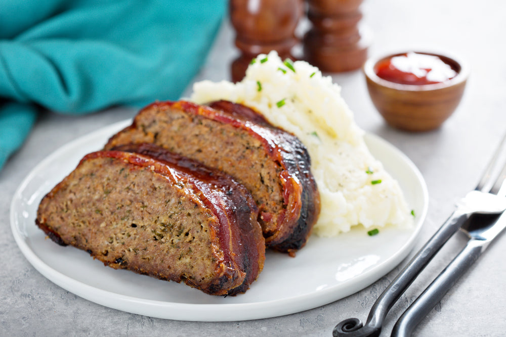 Two slices of meatloaf on a white plate with mashed potato