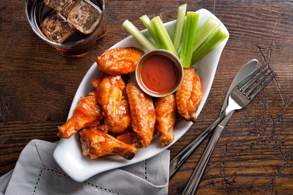 A bowl of chicken wings with a container of homemade hotsauce
