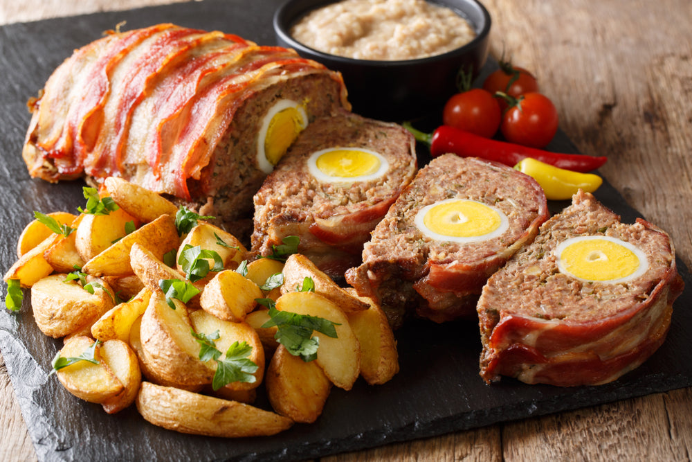 Classic german meatloaf with potato wedges and bacon next to sauce on a plate