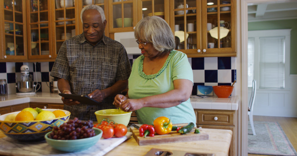 Elderly couple smiling in the kitchen as they prepare a meal using an ipad for directions
