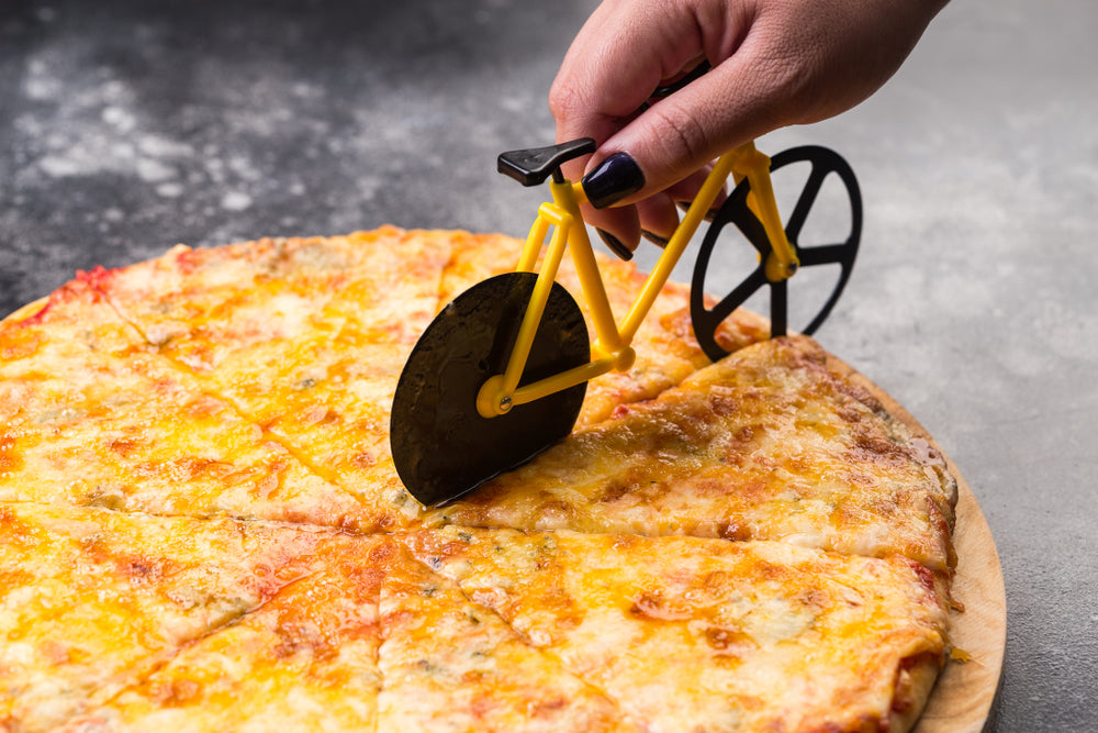 A pizza cutter in the shape of a bicycle slicing through a cheese pizza