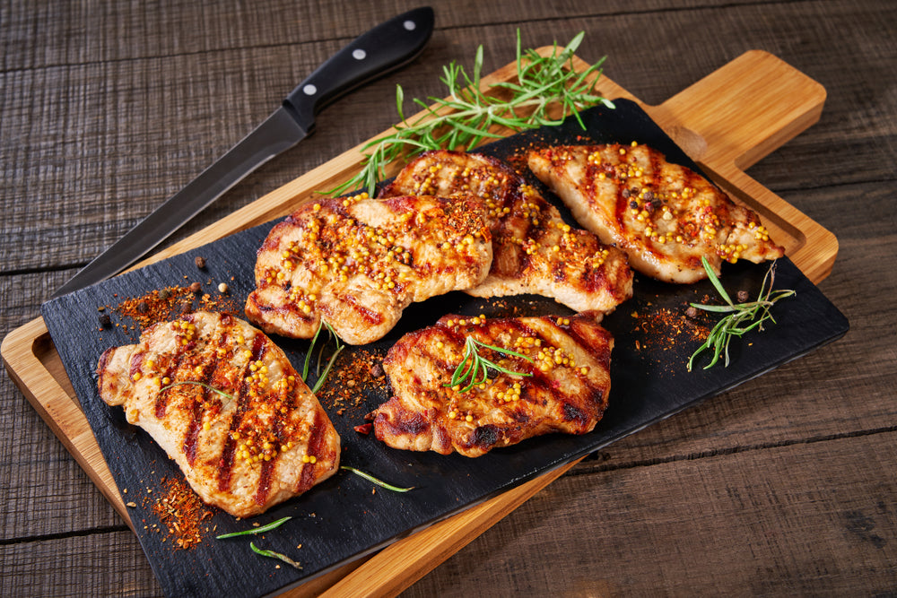 Juicy apple cider glazed pork chops on a square wooden cutting board on a dark surface