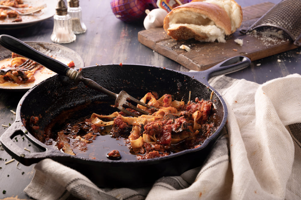 Mess after leftover meal eating Pasta Fettuccine and meatball casserole in cast iron skillet