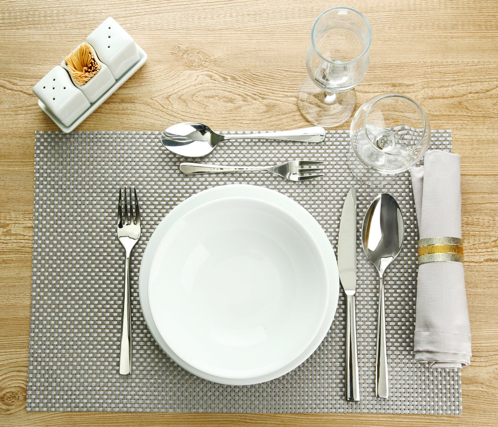 Top view of a table set for dinner with grey place mat white plates and silver utensils